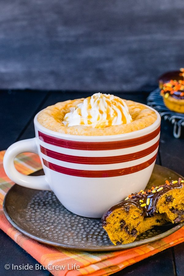 A white mug filled with salted caramel pumpkin latte and topped with whipped cream and caramel drizzles