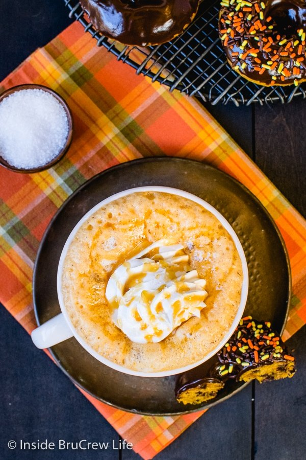 Overhead picture of a mug on an orange towel filled with salted caramel pumpkin latte and topped with whipped cream
