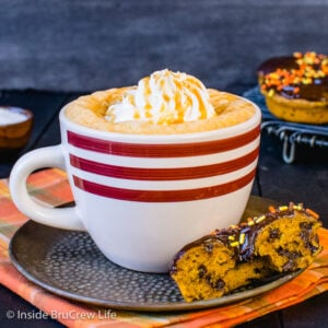 A white mug filled with salted caramel pumpkin latte and topped with whipped cream and caramel