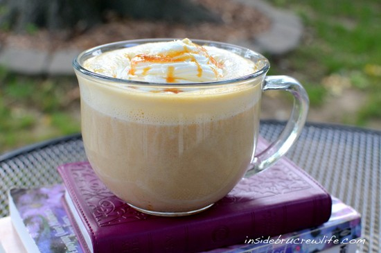 A clear mug filled with Salted Caramel Pumpkin Latte and topped with whipped cream