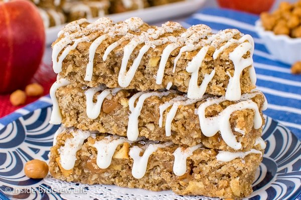 Three caramel apple granola bars drizzled with white chocolate stacked up on a blue plate