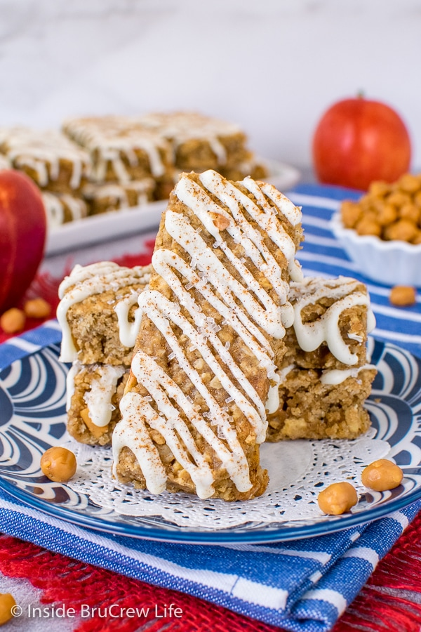 A blue plate with a few homemade apple granola bars drizzled with white chocolate on it with one standing up