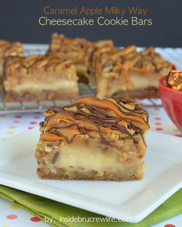 A square of Caramel Milky Way Cheesecake Cookie Bars on a white plate with a wire rack behind it with more cookie bars on it