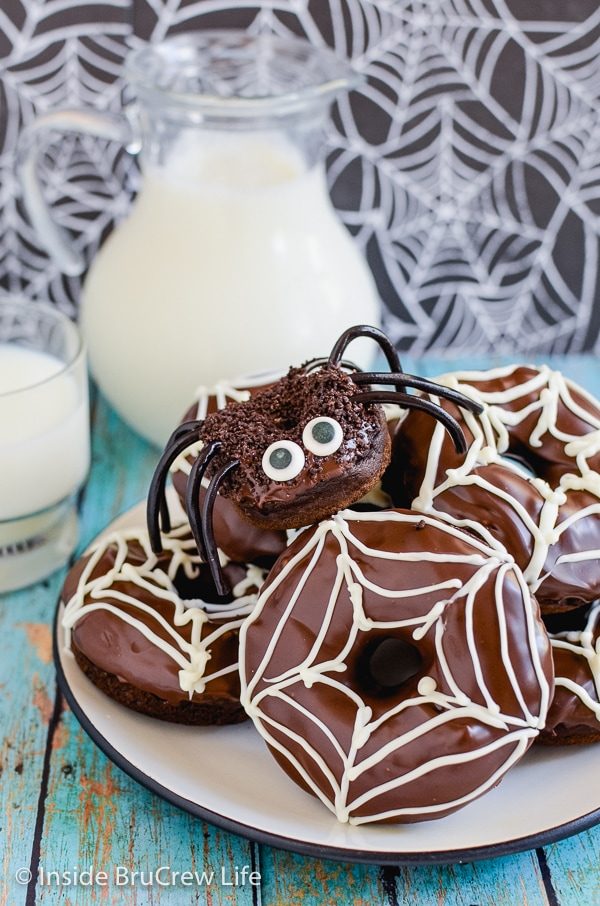 A white plate with chocolate pumpkin donuts decorated like spiders and spiderwebs piled on it