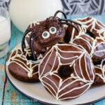 A white plate with chocolate pumpkin spider donuts stacked on it