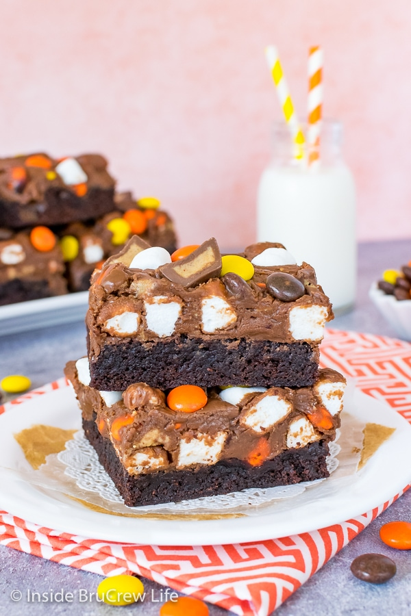 A white plate on an orange and white towel with two fluffernutter fudge brownies on it and bottle of milk behind it