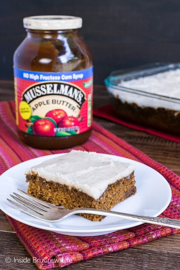 A slice of apple butter cake on a white plate with a jar of Musselman's apple butter behind it