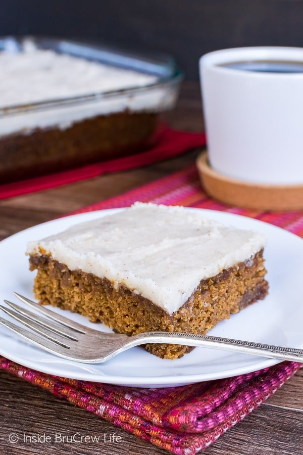 A slice of apple butter cake on a white plate with a cup of coffee and the full cake behind it