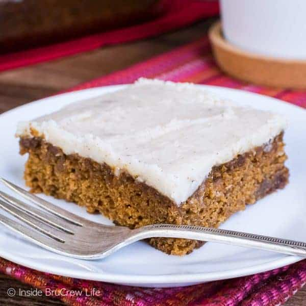 A slice of apple butter cake on a white plate with a fork