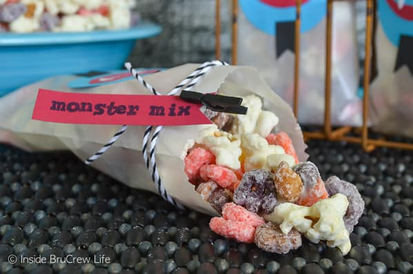 Monster Mix Popcorn - popcorn, cereal, peanuts, and candy covered in white chocolate makes a fun treat for Halloween parties! #snackmix #popcorn #candycorn #peanuts #whitechocolate #halloween #halloweenparties