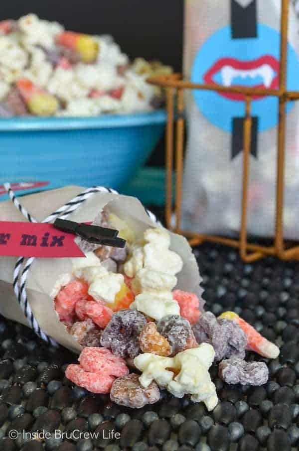 Monster Mix Popcorn - this easy snack mix is full of marshmallows, peanuts, Halloween cereal, and candy corn. Perfect no bake treat for Halloween parties! #snackmix #popcorn #candycorn #peanuts #whitechocolate #halloween #halloweenparties