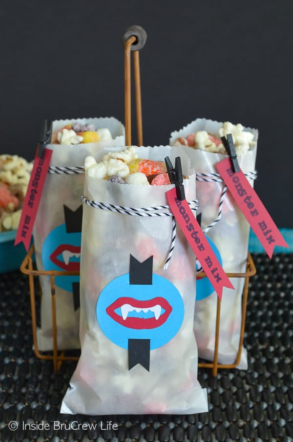 Monster Mix Popcorn - this white chocolate covered snack mix makes a great treat for Halloween parties. Great recipe to munch on while watching movies too! #snackmix #popcorn #candycorn #peanuts #whitechocolate #halloween #halloweenparties