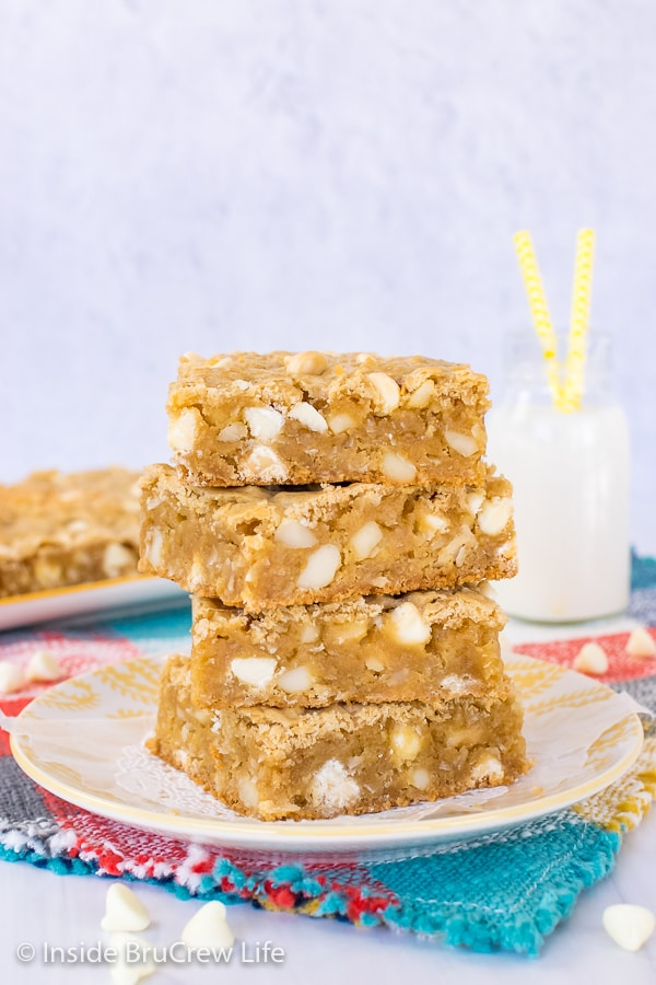 Four tropical blonde brownies stacked up on a white and yellow plate with more blondies behind it