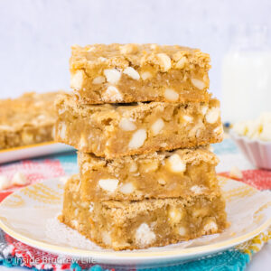 A stack of four tropical blonde brownies on a white and yellow plate