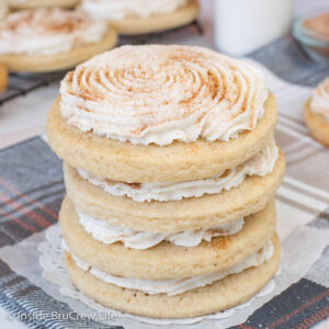 A stack of four churro cookies topped with cinnamon frosting and cinnamon sugar.
