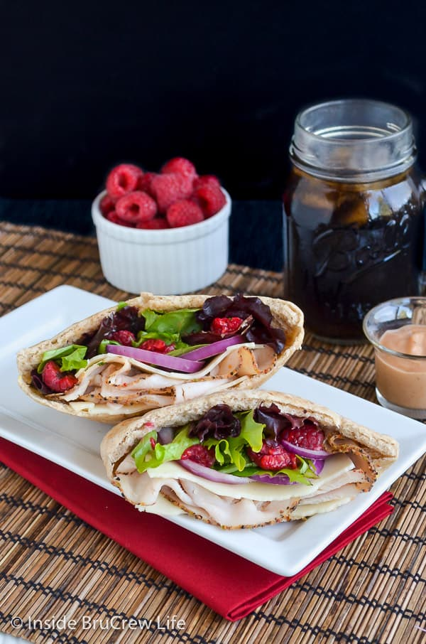Two pita halves filled with turkey, raspberries, and salad on a white plate