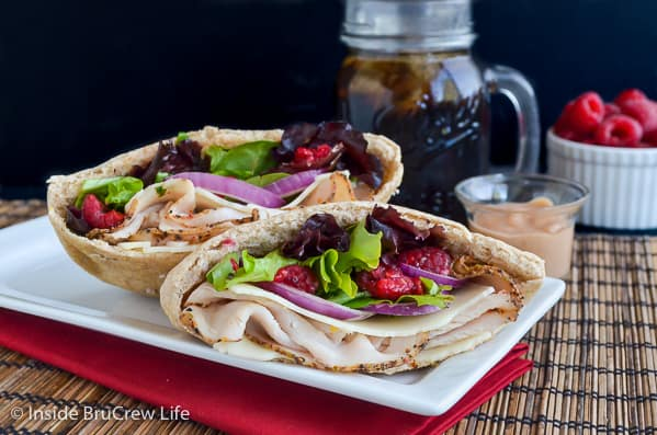 Two pita halves on a white plate filled with turkey, salad, onions, and raspberries