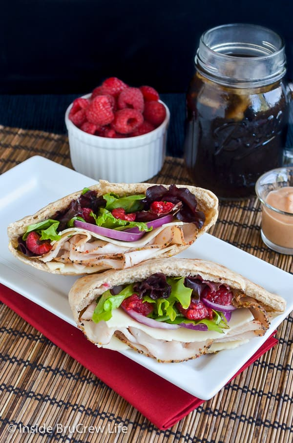 Overhead picture of two pita halves filled with turkey, salad, and raspberries