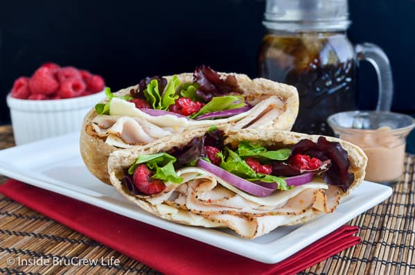 A white plate with two pita halves filled with turkey, salad, and raspberries