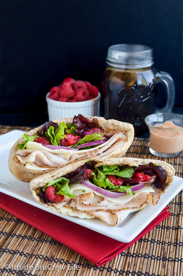 Two pita halves on a white plate filled with turkey, cheese, spring mix, and raspberries