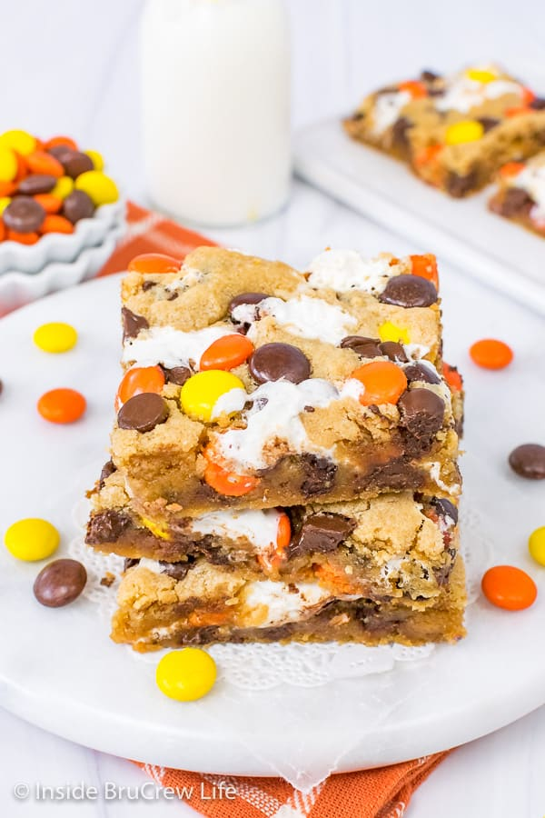 An overhead picture of three squares of Marshmallow Reese's Blonde Brownies on a white board with Reese's scattered around it