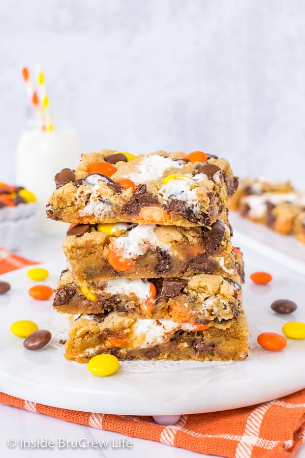 Four squares of peanut butter blondies stacked up on a white board with Reese's Pieces scattered around it