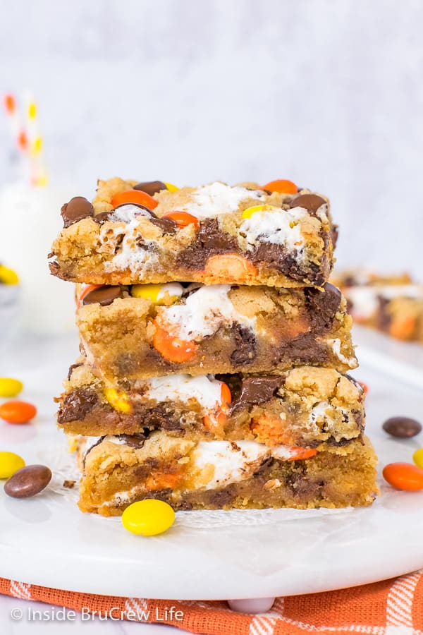 A stack of four peanut butter blonde brownies loaded with chocolate chips, marshmallow, and Reese's Pieces on a white board