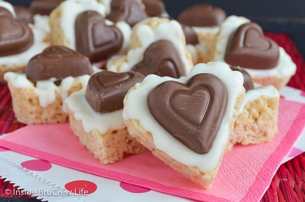 White Chocolate Reese's Krispie Hearts - a peanut butter cup heart and white chocolate make these the best rice krispie treats. Make this easy no bake recipe for Valentine's day this year. #ricekrispietreats #nobake #peanutbuttercups #heartshapedtreats #valentinesday #reeses