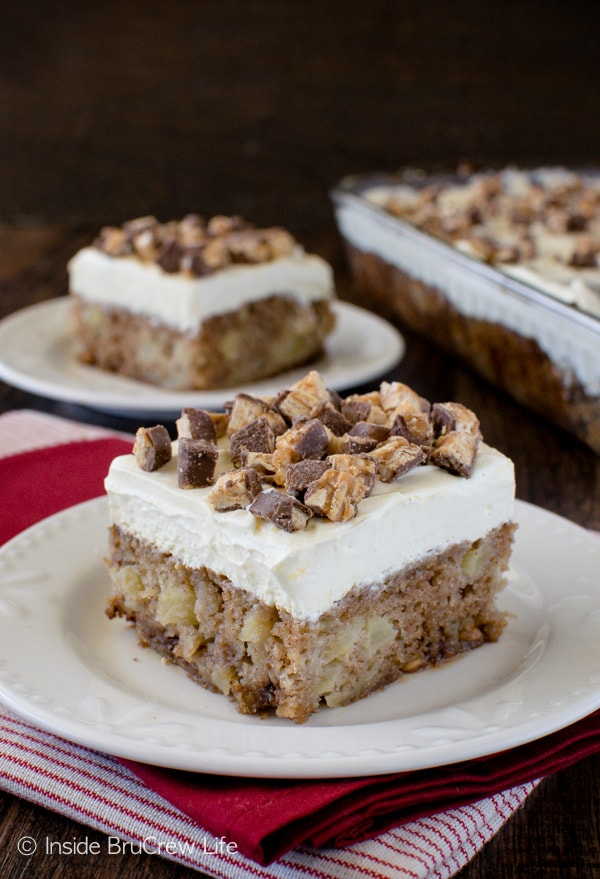 Two squares of apple snickers cake on white plates with a pan of cake beside them