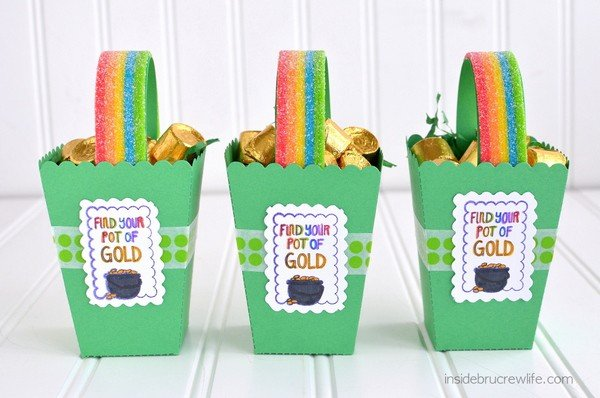 Three green St. Patrick's Day boxes lined up and filled with Rolos and rainbow candy handles