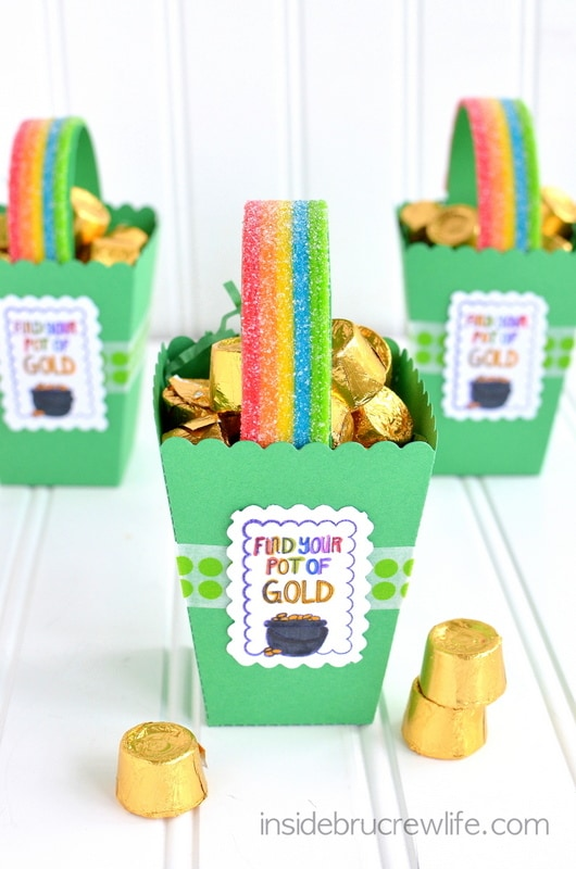 Rainbow candy stips and gold Rolos inside three popcorn boxes