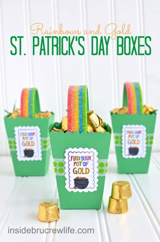 Three green St. Patrick's Day boxes with a rainbow candy handle and chocolate gold candies