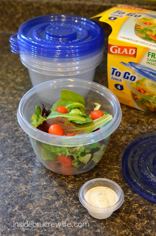 A clear plastic container filled with salad