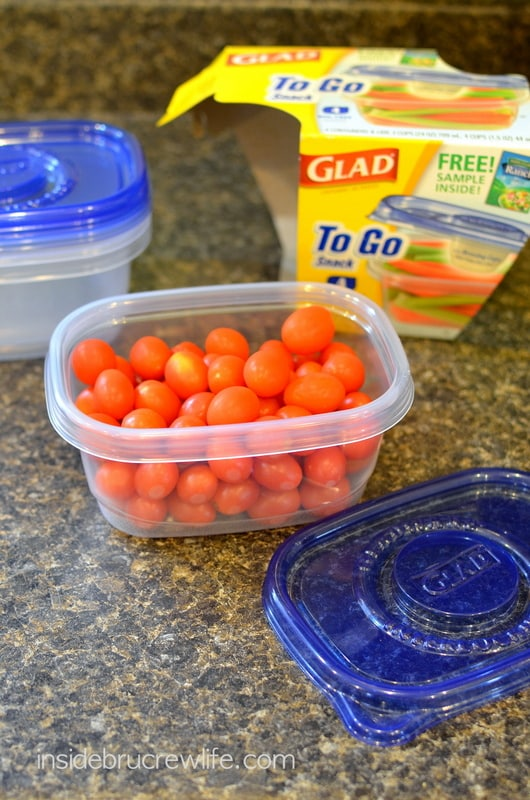 A clear plastic container filled with cherry tomatoes