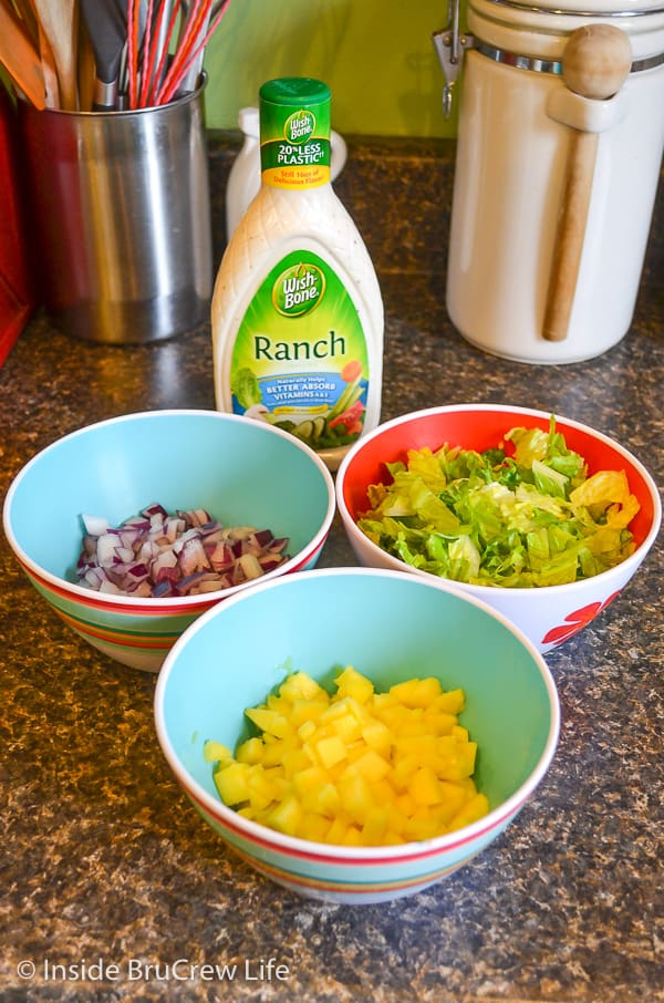 Three bowls filled with chopped mangos, onions, and lettuce and a bottle of ranch dressing behind them