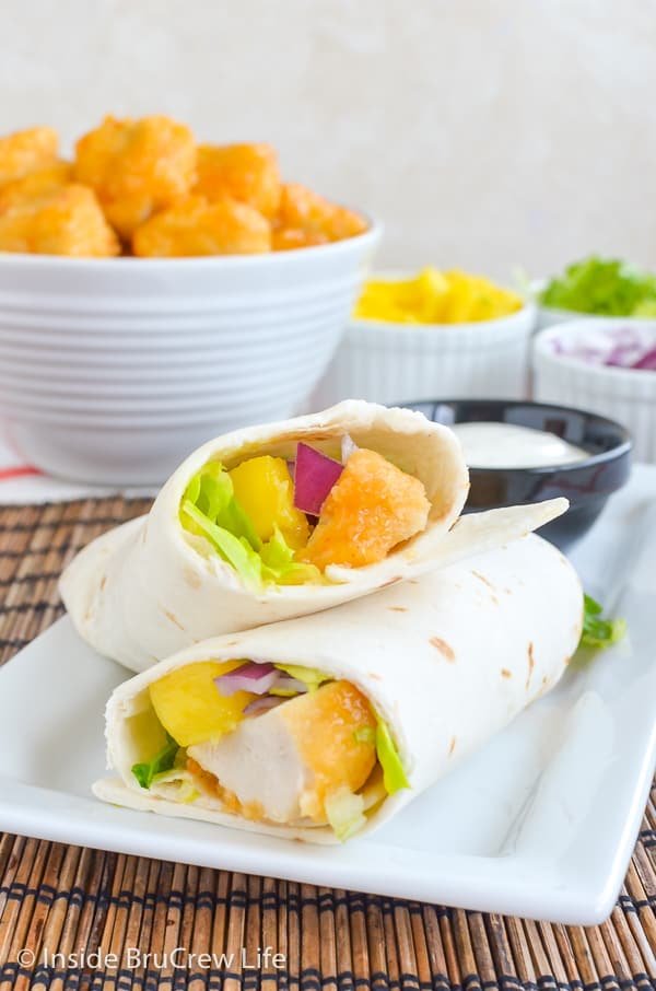 A white plate with a mango chicken wrap cut in half and leaning on its side and bowls of toppings behind it