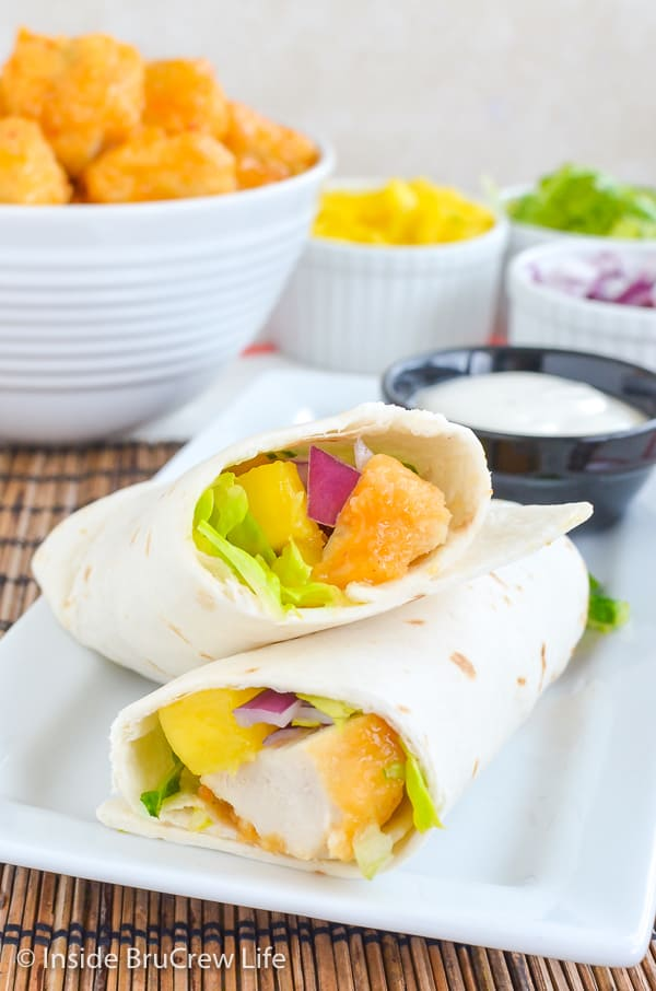 A white plate with a mango chicken wrap cut in half and propped up on its side