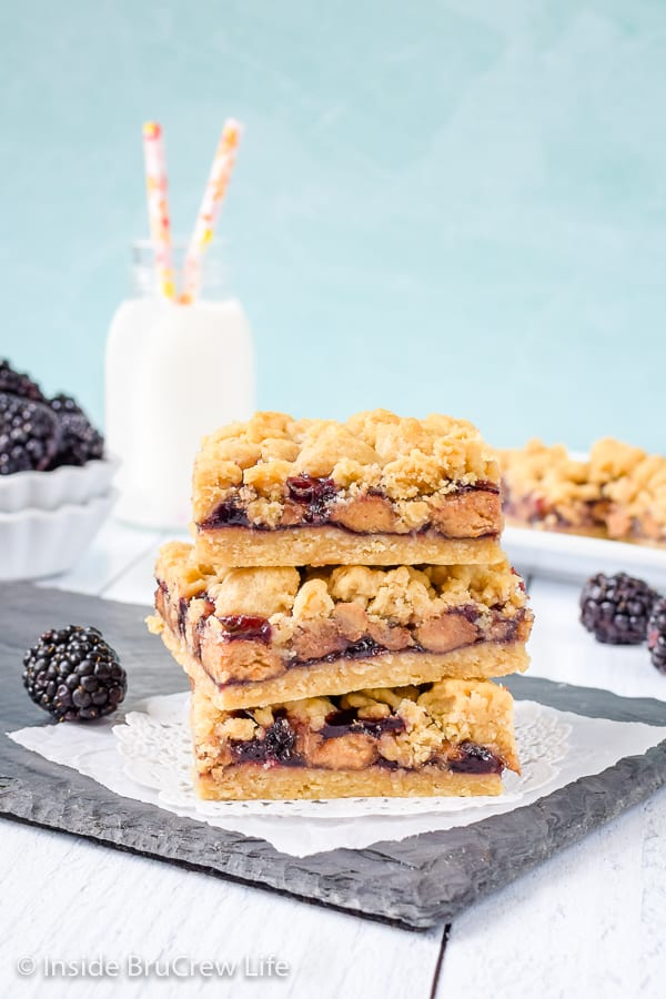 Peanut Butter and Jelly Crumb Bars - these sweet peanut butter and jelly bars are full of peanut butter cups and blackberry preserves. Easy dessert recipe! #peanutbutterandjelly #cookiebars #peanutbuttercups #blackberry #backtoschool