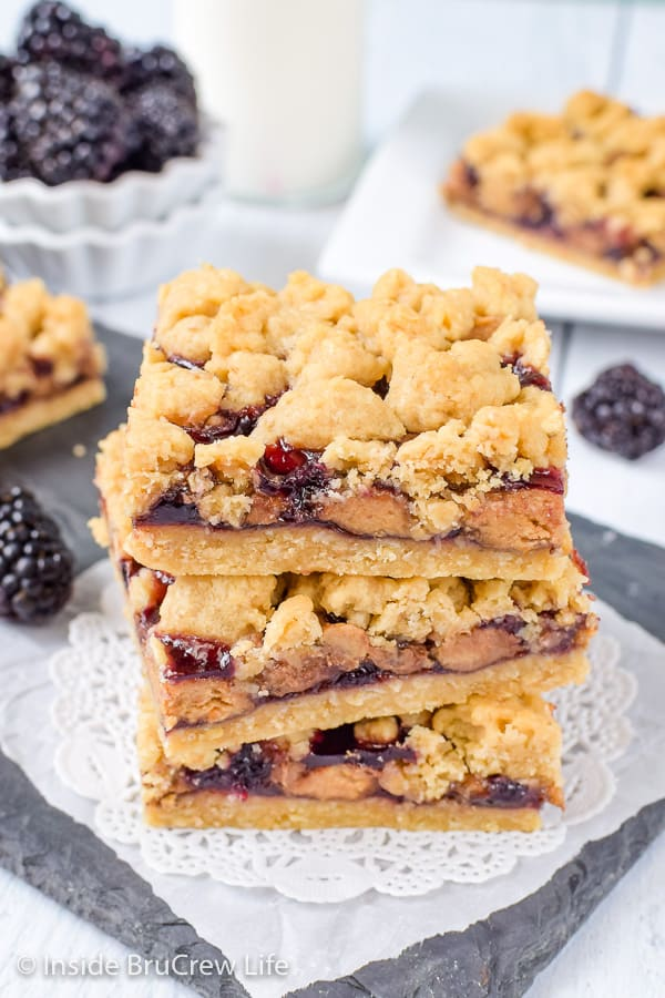 Peanut Butter and Jelly Crumb Bars - peanut butter cups and blackberry preserves add a fun peanut butter and jelly twist to these crumble bars. Try this easy recipe for a fun dessert or after school snack! #peanutbutterandjelly #cookiebars #peanutbuttercups #blackberry #backtoschool