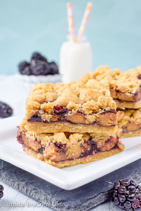 Peanut Butter and Jelly Crumb Bars - peanut butter cups and blackberry preserves give these easy crumble bars a fun peanut butter and jelly twist! Easy recipe for dessert or after school snacks. #peanutbutterandjelly #cookiebars #peanutbuttercups #blackberry #backtoschool