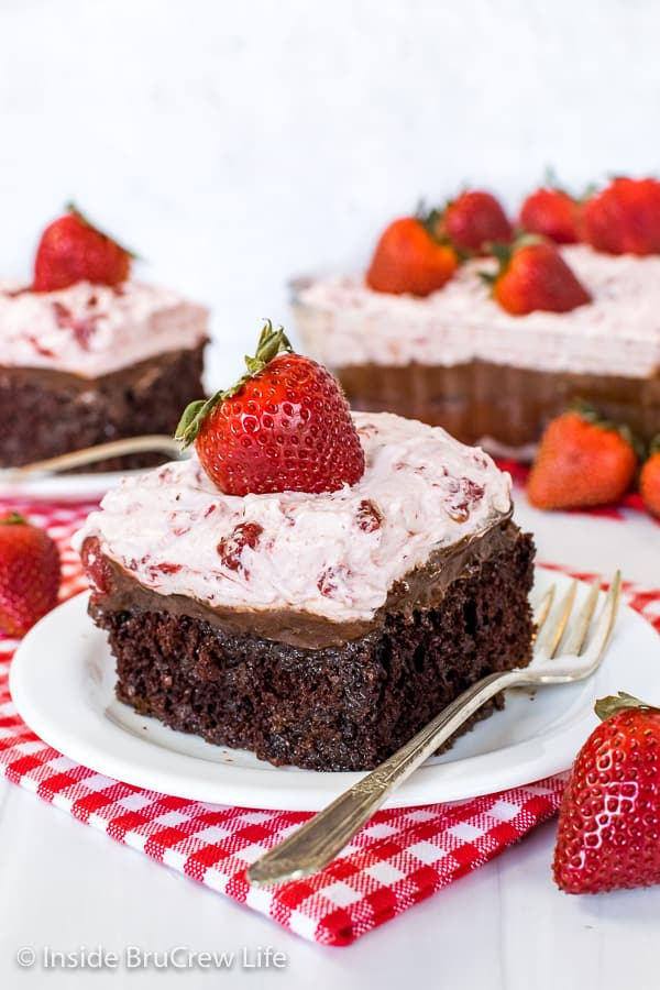 Two white plates with strawberry fudge poke cake slices on them and fresh strawberries on top