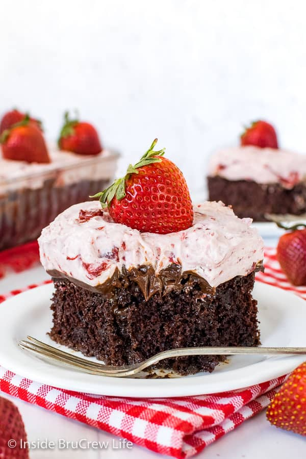 A white plate with a piece of strawberry fudge poke cake on it with a bite missing in the front of the cake