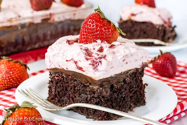 A close up pictures of a slice of strawberry fudge poke cake on a white plate with a fork beside it