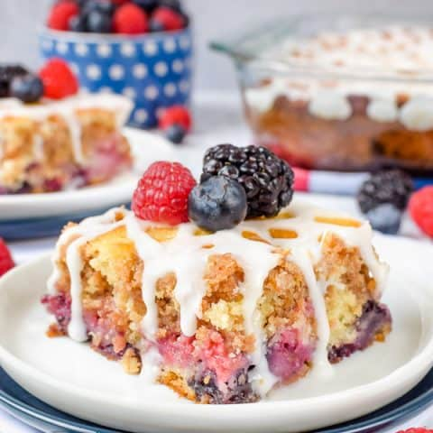 A white plate with a square of triple berry coffee cake topped with fresh fruit on it