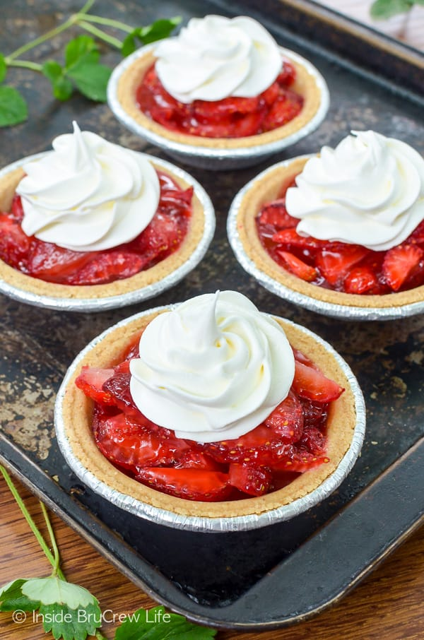 Mini Strawberry Pies - little graham cracker crusts filled with fresh strawberries and strawberry glaze makes an awesome dessert. Make this easy recipe for spring and supper picnics and parties! #strawberry #pie #grahamcrackercrust #minidesserts #summer #mothersday #easy #recipe #fourthofjuly