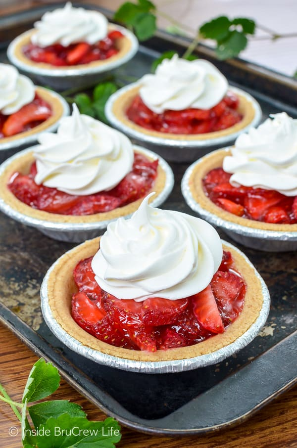 Mini Strawberry Pies -little graham cracker crusts filled with fresh strawberries and strawberry glaze. Make this easy recipe for spring or summer picnics and parties! #strawberry #pie #grahamcrackercrust #minidesserts #summer #mothersday #easy #recipe #fourthofjuly