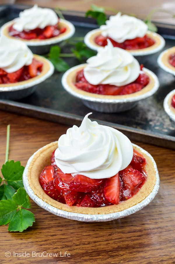 Mini Strawberry Pies -fresh strawberries in a graham cracker crust with strawberry Jello and Cool Whip. Try this easy recipe for spring and summer parties! #strawberry #pie #grahamcrackercrust #minidesserts #summer #mothersday #easy #recipe #fourthofjuly