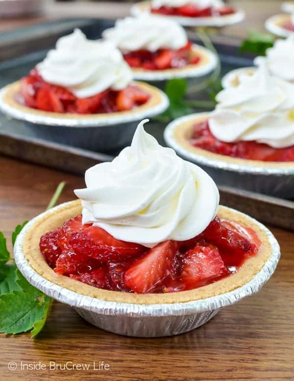 Mini Strawberry Pies - fresh strawberries in a graham cracker crust makes a fun and delicious dessert. Make this easy recipe for spring and summer parties! #strawberry #pie #grahamcrackercrust #minidesserts #summer #easy #recipe #fourthofjuly