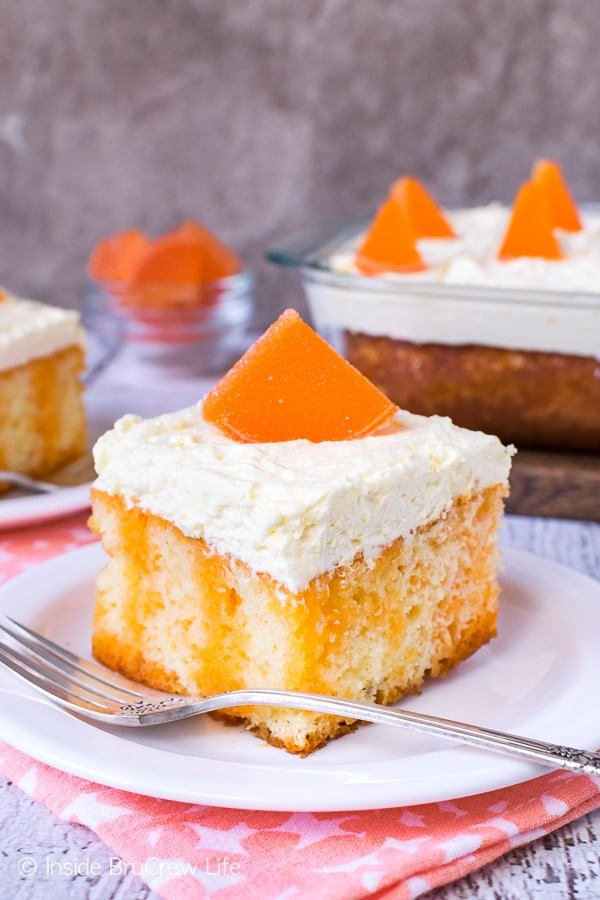 Orange Creamsicle Poke Cake - stripes of orange Jello and a fluffy vanilla mousse frosting makes this orange creamsicle cake perfect for summer parties. Easy recipe to make for picnics. #cake #orange #summerdessert #recipe #jellocake #puddingfrosting