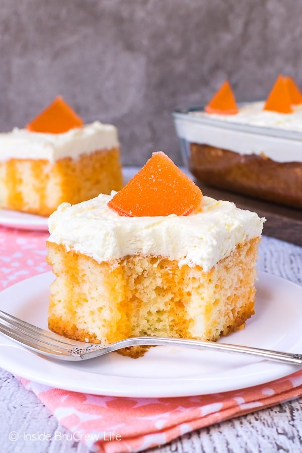 Orange Creamsicle Poke Cake - this easy creamsicle cake has orange Jello stripes and a fluffy pudding frosting. Perfect poke cake recipe for summer picnics and parties! #cake #orange #summerdessert #recipe #jellocake #puddingfrosting